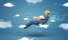 Lustiges racedriver junger Mann, der zwischen Wolkenkonzept fährt Stockfotografie