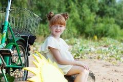Lustiges rothaariges kleines Mädchen, das mit Fahrrad aufwirft Stockfoto