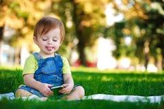 Lustiges Schätzchen spielt mit Telefon Stockbilder