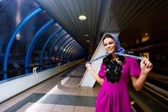 Lustiges schönes Mädchen, das im purpurroten Kleid lächelt stockbilder