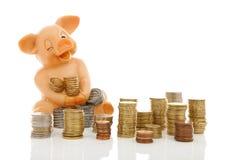 Lustiges Sparschwein und Stapel von Münzen Stockfotos