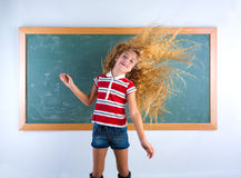 Lustiges Studentenmädchen, das in der Schule langes Haar leicht schlägt Stockbilder
