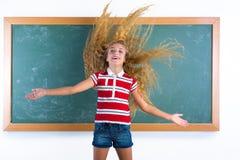Lustiges Studentenmädchen, das in der Schule langes Haar leicht schlägt Stockfotos