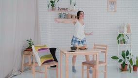 Lustiges Tanzen der jungen Frau in tragenden Pyjamas der Küche morgens Brunettemädchen in der frohen Stimmung hört Musik Lizenzfreie Stockfotografie