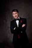 Lustiges tragendes Smoking des jungen Mannes auf grauem Hintergrund Lizenzfreies Stockbild