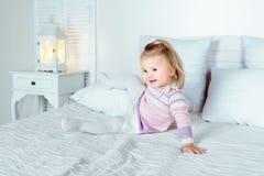 Lustiges und nettes blondes kleines lächelndes Mädchen, das auf Bett spielt Stockfoto