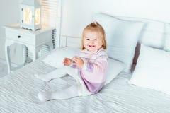 Lustiges und nettes blondes kleines lachendes Mädchen, das auf Bett spielt Stockfotos