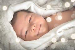Lustiges und nettes lächelndes Baby, das Kamera betrachtet Lizenzfreie Stockfotos