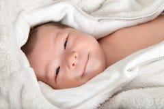 Lustiges und nettes lächelndes Baby, das Kamera betrachtet Stockfotografie