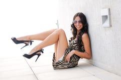 Lustiges weibliches Baumuster an der Art und Weise, die auf dem Fußboden sitzt Stockfotos