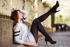 Lustiges weibliches Modell der Mode mit den hohen Absätzen, die auf dem flo sitzen Stockbild