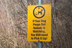 Lustiges Zeichen, das Wanderer erinnert, nach ihren Hunden aufzuheben Lizenzfreie Stockfotos