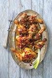 Lustrata piccante ed il bacon hanno avvolto le coscie di pollo al forno con le cipolle ed il peperoncino rosso fotografia stock libera da diritti