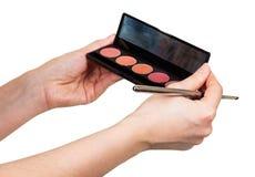 Lustre de lèvre de palette et brosse cosmétique dans des mains femelles d'isolement Photos stock