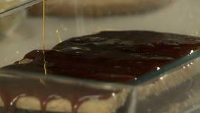 Lustre de versement de chocolat de chef sur les pains grillés croquants banque de vidéos