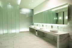 Lustro, baseny i faucets w wygodnej jawnej toalecie, zdjęcia stock