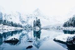 Lustrzana powierzchnia zimy jezioro z pasmem górskim Fotografia Stock
