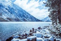 Lustrzana powierzchnia zimy jezioro z pasmem górskim Obraz Royalty Free