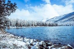 Lustrzana powierzchnia zimy jezioro z pasmem górskim Zdjęcia Royalty Free