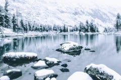 Lustrzana powierzchnia zimy jezioro z pasmem górskim Obrazy Stock