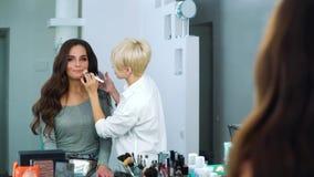 Lustrzany odbicie stosuje proszek na młodej kobiety twarzy przy piękno salonem makeup artysta zdjęcie wideo