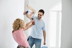 Luta brincalhão dos pares ao pintar a casa nova imagem de stock