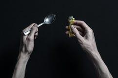 A luta contra drogas e assunto da toxicodependência: as mentiras do viciado da mão em uma tabela escura e em torno dela são droga Fotografia de Stock