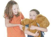Luta da rapariga e do menino sobre o urso imagens de stock royalty free