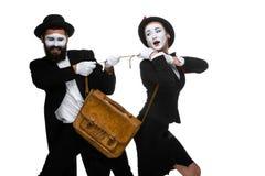 Luta do homem e da mulher de negócio sobre a pasta Foto de Stock