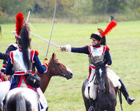 Luta dos soldados-reenactors em cavalos de equitação das espadas Imagem de Stock