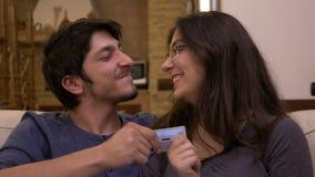 Luta giggling dos pares novos felizes sobre o cartão de crédito e beijo no sofá em casa vídeos de arquivo