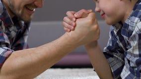 Luta romana de braço do pai e do filho, jogando os jogos, passando o tempo junto, amizade video estoque
