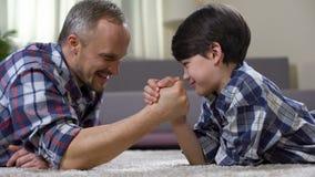Luta romana de braço loving no assoalho, lazer do pai e da criança do fim de semana em casa, divertimento filme