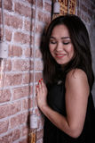 Lutade den asiatiska flickan för ung glamour med stängda ögon till tegelstenväggen arkivfoto