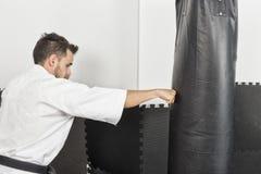 Lutador atlético do karaté que dá um pontapé vigoroso do pé a um b pesado Foto de Stock Royalty Free