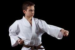 Lutador do karaté no quimono branco isolado no preto imagem de stock
