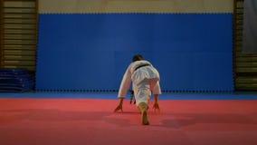 Lutador que salta e que faz uma sequência do kata do karaté no dojo no movimento lento filme