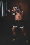 Lutador tailandês descamisado novo de Muay com as luvas de encaixotamento que exercitam com saco de perfuração Fotografia de Stock