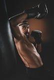 Lutador tailandês novo agressivo de Muay nas luvas de encaixotamento que treinam o encaixotamento tailandês Fotografia de Stock