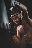 Lutador tailandês novo determinado de Muay nas luvas de encaixotamento que treinam o encaixotamento tailandês com saco de perfura Fotografia de Stock Royalty Free