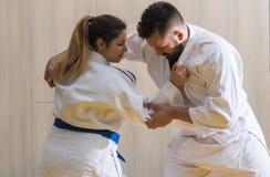 Lutadores do judô da mulher e do homem no salão de esporte Imagem de Stock