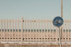 Lutande cykeltrafiksignal och järnväg staketbakgrund royaltyfria bilder