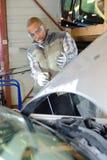 Lutande mekaniker tillbaka att se bilmotorn arkivbilder
