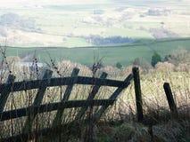Lutande staket i en fridsam lantlig sikt för fält Royaltyfria Bilder