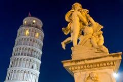 Lutande torn av Pisa med statyn efter solnedgång Arkivbild