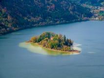 Lutandeförskjutningsbild av en ö i Schliersee sjön i höst arkivfoton