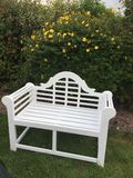 Lutchens bench on a lawn. White ornate bench on a lawn Royalty Free Stock Photo