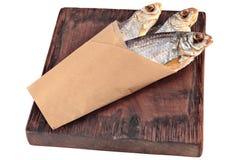 Lutfisk på bruntfyrkantträbrädet som slås in i papper, isolat Royaltyfri Foto
