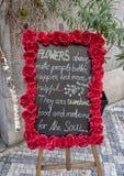 Luther Burbanks au sujet des fleurs écrites sur un panneau de craie entouré par les roses rouges à Prague, République Tchèque image libre de droits