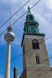 Lutheran Sts Mary kyrka i Berlin i motsats med visartornet av kommunikationer arkivfoto
